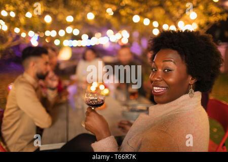Portrait happy woman drinking wine, enjoying dinner garden party - Stock Image