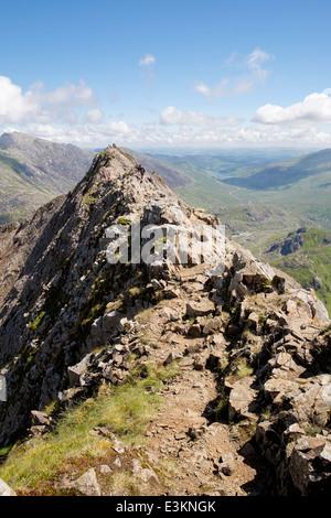 View back along red rocks on Crib Goch summit ridge top at start of Snowdon Horseshoe in mountains of Snowdonia - Stock Image