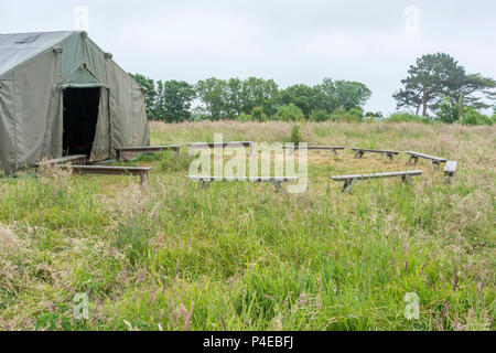 Field tent with circle of small bench seating, with copy space. Metaphor for meeting place, sitting round in a circle, circular discussions, etc. - Stock Image
