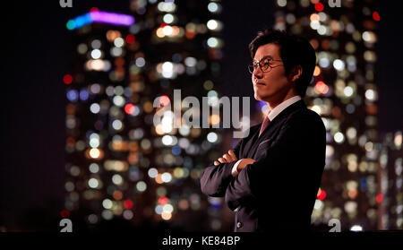 Side view portrait of businessman posing against night view of city - Stock Image