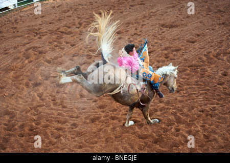 Horse trying to throw rodeo cowboy member of PRCA from its back in Smalltown Texas Bridgeport - Stock Image