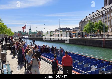 Tourists' canal cruise boat by Christiansborg Palace on Slotsholmen or Castle Isle in Copenhagen, Zealand, Denmark, - Stock Image