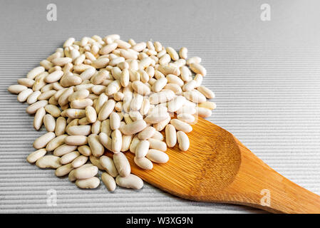 Haricot beans with wooden spoon isolated on table background with copy space - Stock Image
