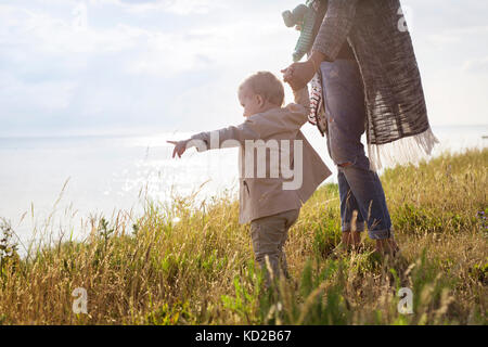 Mother walking with son (18-23 months) towards sea - Stock Image