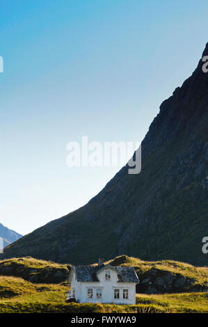 A white house is dwarfed by a steep mountain in the village Hovden on Vesterålen in northern Norway. - Stock Image