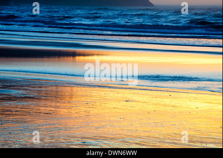 Sunset is reflected in the wet sand on Cape Lookout Beach on the Oregon Coast. - Stock Image