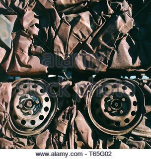 Crushed motor vehicles, showing the remains of two wheels. Birmingham, UK. - Stock Image