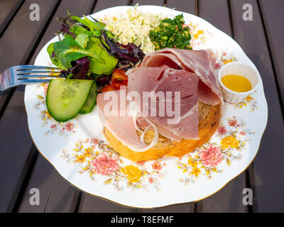 Café lunch Honey Roast  ham open sandwich with English mustard and salad garnish served outdoors - Stock Image