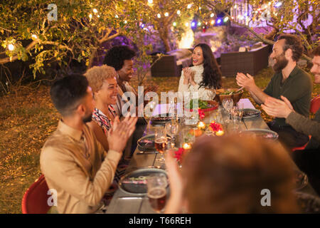 Friends clapping, enjoying dinner garden party - Stock Image