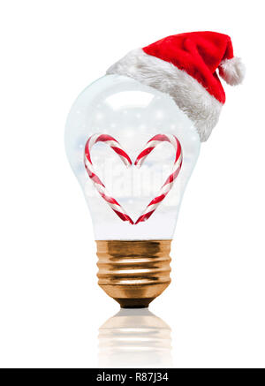 Snow globe light bulb wearing Santa hat with romantic heart shape candy cane and copy space. Glowing Xmas season and bright New Year. - Stock Image
