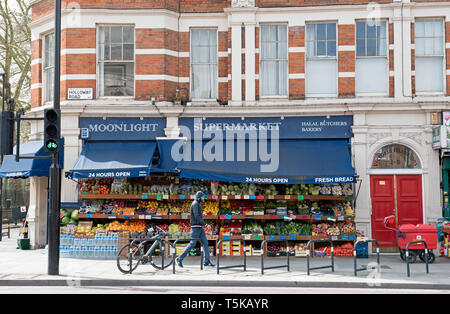 Moonlight Supermarket with man passing, Holloway Road, London Borough of Islington. - Stock Image