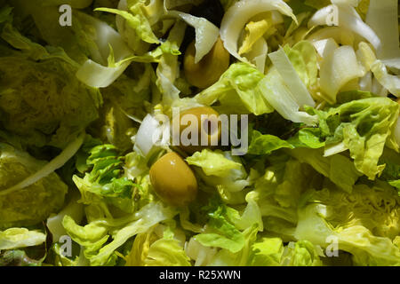 Fresh green salad garnished with green olives - Stock Image