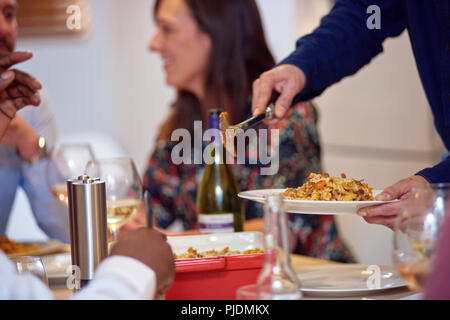 Friends talking, man serving food at dinner party - Stock Image