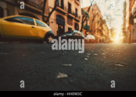 Wide angle view from  asphalt level on narrow street of Barcelona with cars, taxi and sun, shallow depth of field, - Stock Image