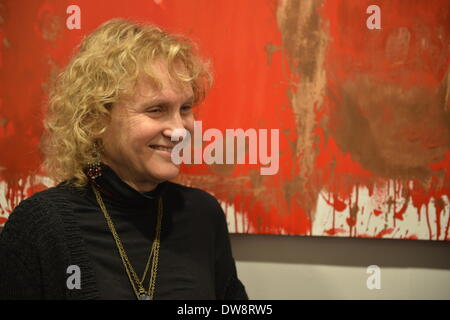 Huntington, New York, U.S. - March 1, 2014 - At the Opening  Reception '3 Wild and Crazy Artists' at FotoFoto Gallery, a woman visitor smiles at the exhibit 'Red & White Paintings & Photographs – El Vocio Existential' by artist Barry Feuerstein. - Stock Image