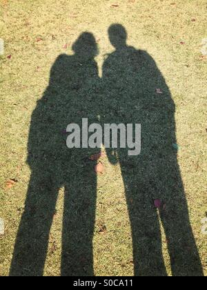 Shadow silhouette of couple on green grass. - Stock Image