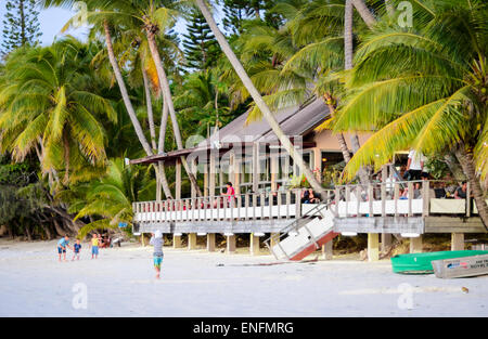 Rustic beach restaurant sheltered by palm trees, on a beautiful tropical island. Isle of Pines, New Caledonia, South - Stock Image