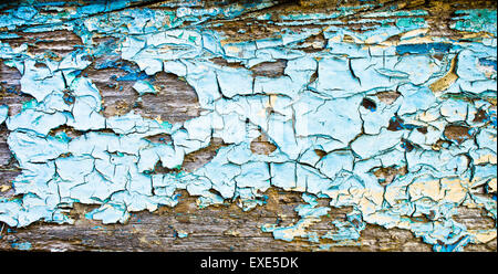 Peeling blue paint on a wooden surface - Stock Image