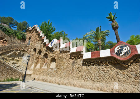 Stoney wall around the perimeter of the Park Guell designed by Antoni Gaudi, Barcelona, Spain - Stock Image