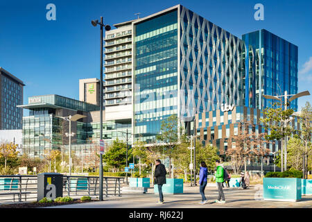 2 November 2018: Salford Quays, Manchester, UK - ITV and BBC buildings on a sunny autumn day, clear blue sky, colourfully dressed young people in... - Stock Image