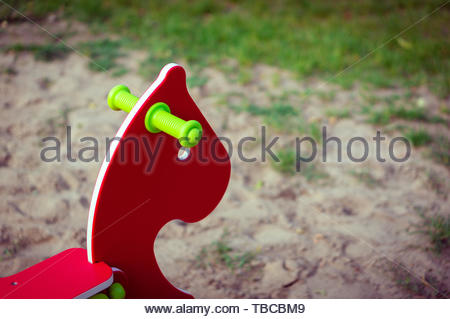 Horse shaped red playground spring swing in soft - Stock Image