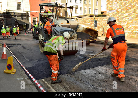 Road resurfacing manual spreading of tarmac and roller going over this and tarmac put down by surfacing machine - Stock Image
