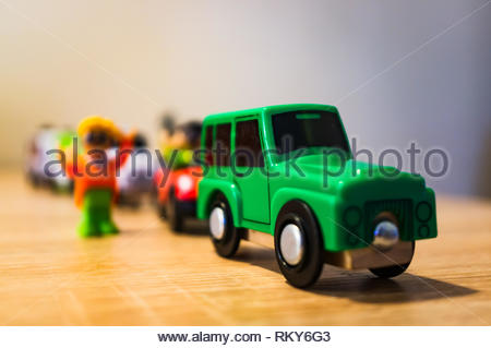 Poznan, Poland - February 9, 2019: Plastic toy cars traffic jam with people standing next to the vehicles in soft focus background. - Stock Image