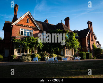 Red Brick Exterior 19th century Victorian Country House. Hotel in early morning sun light Berkshire UK. - Stock Image