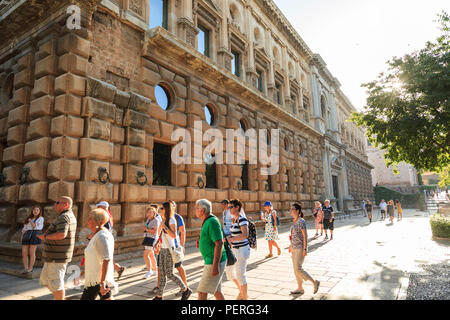 Tourists walking past the outside of the Palace of Carlos V at Alhambra Palace in Granada Spain - Stock Image