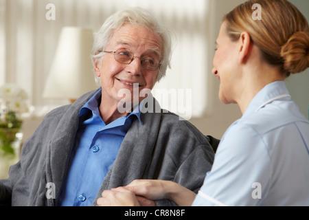 Carer touching senior mans hand - Stock Image