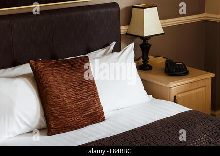 Generic hotel room example with freshly made bed, clean sheets and a plain neutral decor which can be found in any - Stock Image