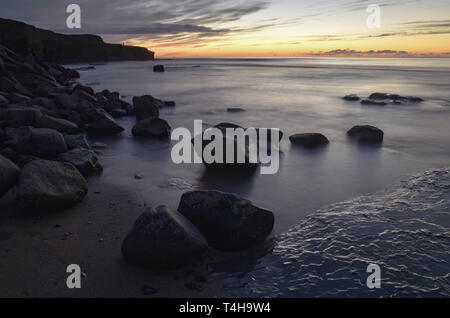 Spectacular, peaceful sunset at low tide, waves breaking over rocks, bright sky reflecting into water, Sunset Cliffs Natural Park, San Diego, CA, USA - Stock Image