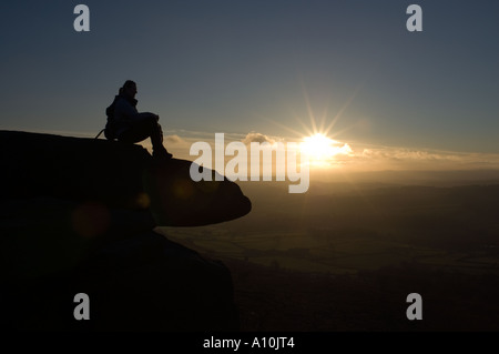 Person looking at the sunset from a crag in the Peak District National Park Derbyshire - Stock Image