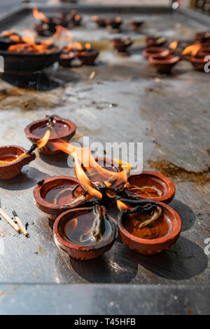 Vertical close up of burning oil lamps at the Kapaleeshwarar Temple in Chennai, India. - Stock Image