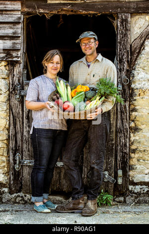 Smiling farmer and woman standing in barn door, holding basket with freshly harvested vegetables, looking at camera. - Stock Image