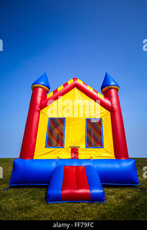 Children's inflatable bouncy castle house in a yard for a fun summer party or event. - Stock Image