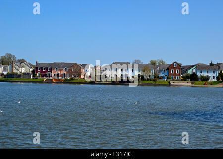 View of the houses across the lake at Watermead, Aylesbury, Buckinghamshire, UK - Stock Image