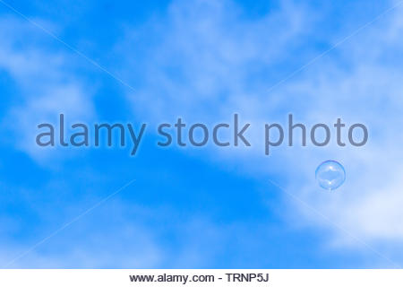 A soap bubble flying in the wind. A beautiful blue sky with some cloud formations serves as background. - Stock Image