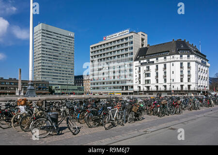 Bicycles outside the central railway station in Copenhagen Denmark Europe with the SAS hotel and arbejdernes landsbank head quarters - Stock Image