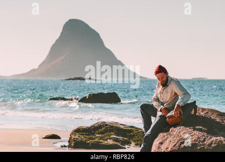 Man with backpack relaxing on beach sea summer trip vacations travel tourist lifestyle adventure journey outdoor in Norway - Stock Image