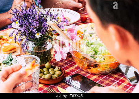 Close up with people friends eating and having fun together having lunch on a table full of food - coloured tasty vegetables and more - seasonal flowe - Stock Image