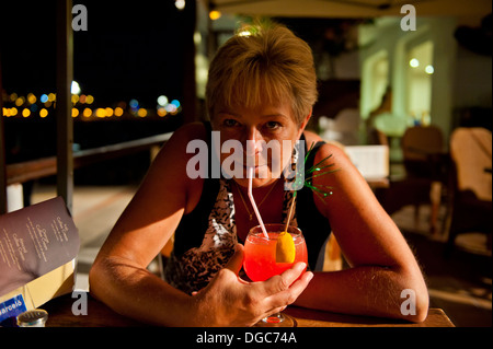 woman enjoying a holiday cocktail - Stock Image