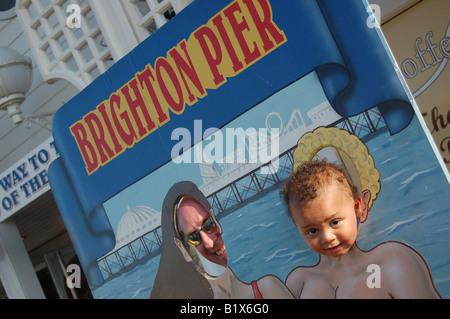 Two people putting their heads through a fairground board, Brighton Pier England - Stock Image