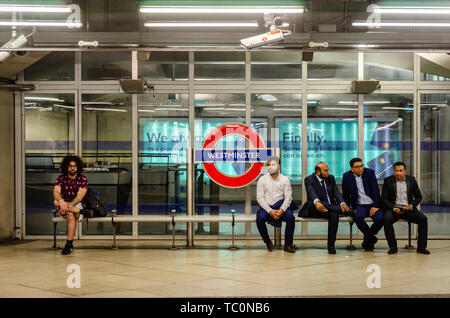 A man sits alone on a bench on the platform at Westminster London Underground Station as a group of Asian men sit together. - Stock Image