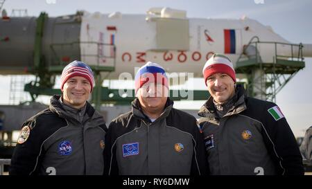 Baikonur, Kazakhstan. 12th Mar, 2019. Expedition 59 backup crew members Drew Morgan of NASA, left, Alexander Skvortsov of Roscosmos, and Luca Parmitano of the European Space Agency, right, pose as the Russian Soyuz MS-12 rocket is transported by train to the launch pad at the Baikonur Cosmodrome March 12, 2019 in Baikonur, Kazakhstan. The Expedition 59 crew: Nick Hague and Christina Koch of NASA and Alexey Ovchinin of Roscosmos will launch March 14th for a six-and-a-half month mission on the International Space Station. Credit: Planetpix/Alamy Live News - Stock Image