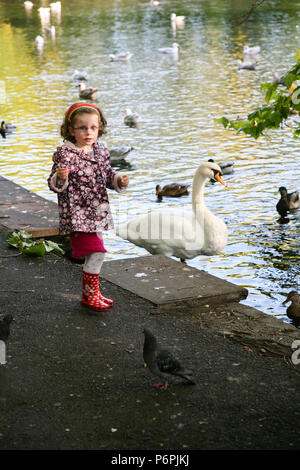 Young girl in red wellington boots playing in the park feeding the birds in Autumn, Dublin, Ireland, Europe. - Stock Image