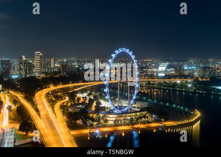 Aerial view of Singapore flyer and city at night in Singapore, Asia. - Stock Image
