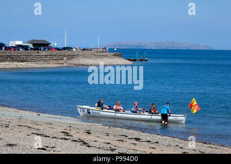Women in a rowing boat beside the shore, Beaumaris, Anglesey, Wales - Stock Image