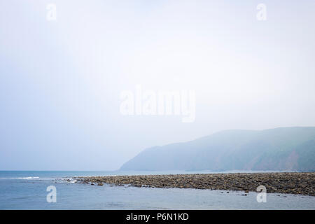 View from the rocky beach at Lynmouth north-east to Foreland Point, North Devon, UK. - Stock Image