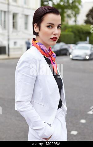 Woman standing in street wearing short white linen jacket - Stock Image